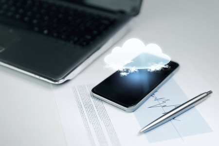 close icon: business, technology and information concept - close up of smartphone with cloud computing icon projection, laptop computer and chart with pen on office table Stock Photo