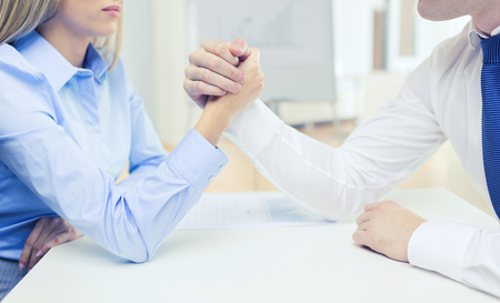 conflicto: business and office concept - businesswoman and businessman arm wrestling during meeting in office