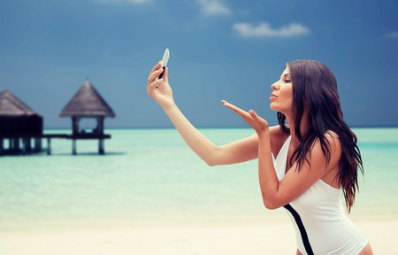 summer, travel, technology and people concept - sexy young woman taking selfie with smartphone and sending blow kiss over bungalow on beach background