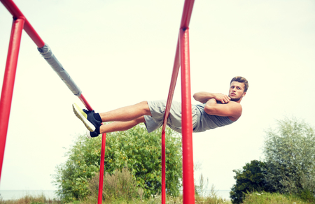 situp: fitness, sport, exercising, training and lifestyle concept - young man doing sit up on parallel bars in summer park