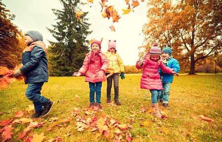childhood, leisure, friendship and people concept - group of happy kids playing with autumn maple leaves and having fun in park photo