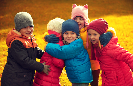 childhood, leisure, friendship and people concept - group of happy kids hugging in autumn park photo