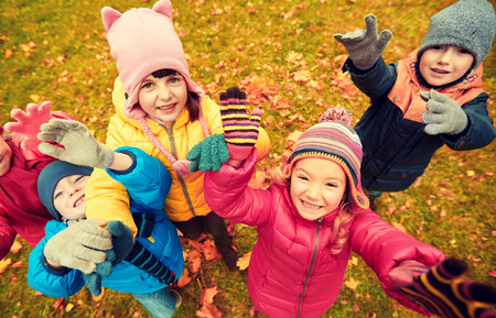 childhood, leisure, friendship and people concept - group of happy children waving hands in autumn park from top photo