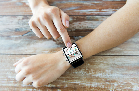 web directories: business, modern technology, internet shopping and people concept - close up of female hands setting smart watch with online shop on screen on wooden table