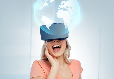 technology, augmented reality, cyberspace, entertainment and people concept - happy amazed young woman with virtual headset or 3d glasses looking at projection of earth globe