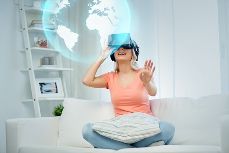 entertainment concept: technology, augmented reality, entertainment and people concept - happy young woman in virtual headset or 3d glasses and headphones playing game at home looking at projection of earth globe