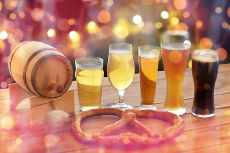 alehouse: brewery, drinks and food concept - close up of different beer glasses, wooden barrel and pretzel on table over holidays lights background