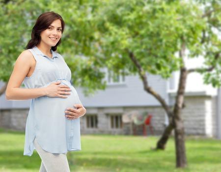 임신, 모성, 사람과 기대 개념 - 여름 정원 및 집 배경 위에 그녀의 큰 뱃속을 만지고 행복 임신 한 여자