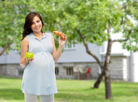 pregnancy, healthy eating, junk food and people concept - happy pregnant woman choosing between green apple and croissant over summer garden and house background