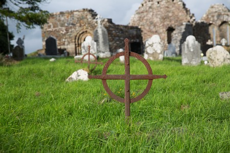 headstones: ancient monument and burial concept - old rusty grave cross, headstones and ruins on celtic cemetery graveyard in ireland Stock Photo