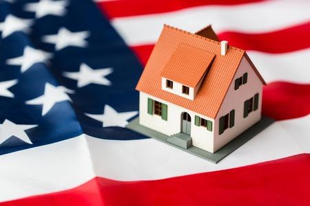 nacionalidad, residencia, propiedad, bienes raíces y concepto de la gente - cerca de vida modelo de casa sobre la bandera americana