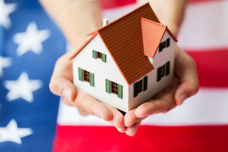 american house: citizenship, residence, property, real estate and people concept - close up of hands holding living house model over american flag