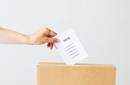 voting, civil rights and people concept - male hand putting vote into ballot box on election Stock Photo