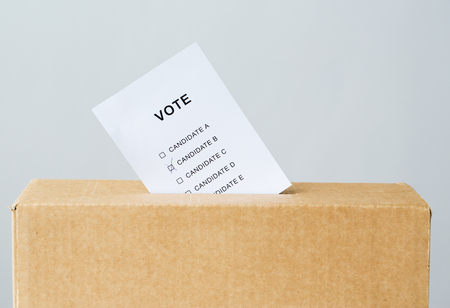 voting and civil rights concept - vote inserted into ballot box slot on election