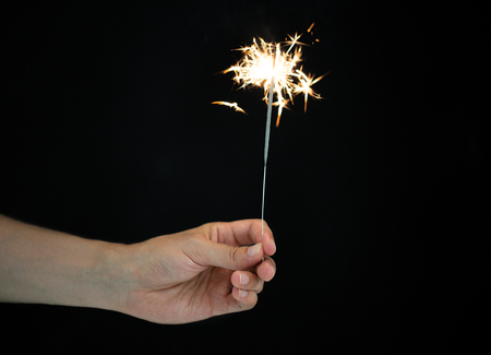 christmas, holidays, new year party and pyrotechnics concept - male hand holding sparkler or bengal light burning over black background Imagens