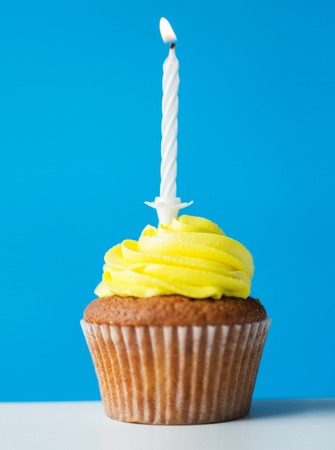 one year: holiday, celebration, greeting and party concept - birthday cupcake with one burning candle over blue background Stock Photo