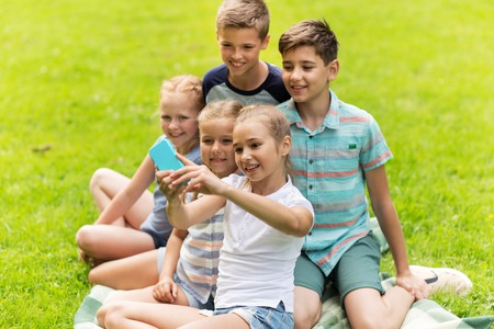 young boys: friendship, childhood, technology and people concept - group of happy kids or friends taking selfie by smartphone in summer park Stock Photo
