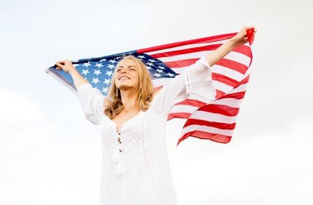 국가, 애국심, 독립 하루 및 사람들이 개념 - 흰색 미국 국기를 야외에서 흰 드레스에 젊은 여자를 행복 하 게 웃 고