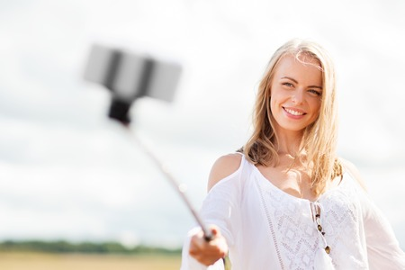 pretty dress: technology, summer holidays, vacation and people concept - smiling young woman in white dress taking picture by smartphone selfie stick on cereal field