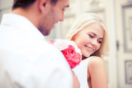 couples in love: summer holidays and dating concept - couple with bouquet of flowers in the city