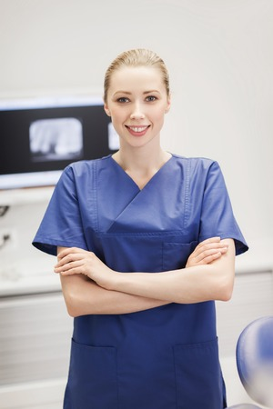personel: people, medicine, stomatology and health care concept - happy female dentist, surgeon or nurse at dental clinic office Stock Photo