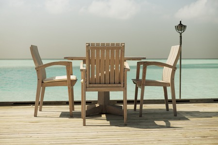 costal: travel, tourism, vacation and summer holidays concept - outdoor restaurant wooden terrace with table and chairs over sea background
