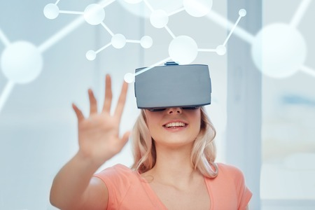 technology, augmented reality, entertainment and people concept - happy young woman with virtual headset or 3d glasses at home looking at projection of molecule Stock Photo