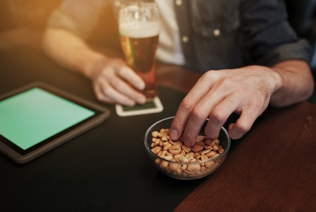 man nuts: people, leisure and technology concept - close up of man with tablet pc computer drinking beer and eating peanuts at bar or pub