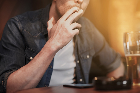bad habit: people, nicotine addiction and bad habits concept - close up of man drinking beer and smoking cigarette at bar or pub Stock Photo
