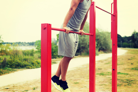 grapple: fitness, sport, exercising, training and lifestyle concept - close up of young man doing pull ups on horizontal bar outdoors