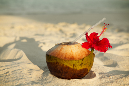 tropical drink: travel, tourism, vacation and summer holidays concept - coconut drink on exotic tropical maldives beach