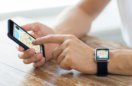business, technology, navigation, location and people concept - close up of male hands on wooden table holding smartphone and wearing smart watch with gps navigator map on screen