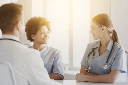health professional: health care, profession, people and medicine concept - group of happy doctors or nurses meeting and talking at hospital