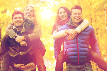 love park: love, friendship, family and people concept - smiling friends having fun in autumn park