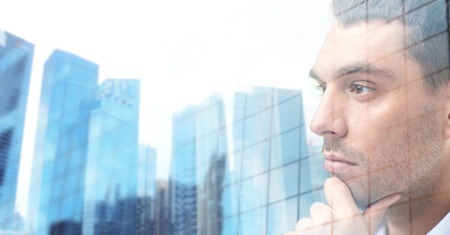 face work: business, people and work concept - close up of businessman male face over office buildings background