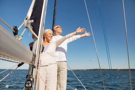 voile: sailing, age, tourism, travel and people concept - happy senior couple hugging on sail boat or yacht deck floating in sea