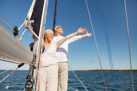 Segeln, Alter, Tourismus, Reisen und Menschen Konzept - glückliche ältere Paar umarmt auf dem Deck Segelboot oder Yacht im Meer schwimmen Standard-Bild - 64378737