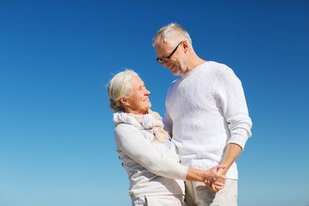 date: Familie, Alter, Reisen, Tourismus und Menschen Konzept - glücklich Senior Paar Hand in Hand am Strand im Sommer Lizenzfreie Bilder