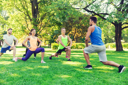 lunge: fitness, sport, friendship and healthy lifestyle concept - group of happy teenage friends or sportsmen exercising and doing lunge at boot camp Stock Photo