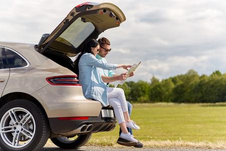 Ocio, viaje por carretera, los viajes y el concepto de la gente - hombre feliz y mujer que busca la ubicación en el mapa sentado en el tronco de un coche con portón trasero al aire libre Foto de archivo - 64370509