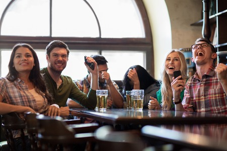 people watching: people, leisure, friendship and entertainment concept - happy friends with smartphones drinking beer and watching sport game or football match at bar or pub Stock Photo
