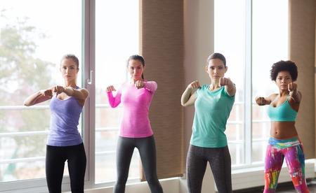 mujeres peleando: fitness, deporte, entrenamiento, gimnasio y artes marciales concepto - grupo de mujeres trabajando y luchando en el gimnasio