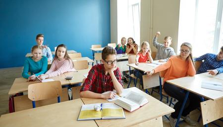 교육, 왕 따, 갈등, 사회 관계 및 사람들이 개념 - 안경 읽기 책을 읽고 학교에서 급우 중 조롱 박해 학생 소년