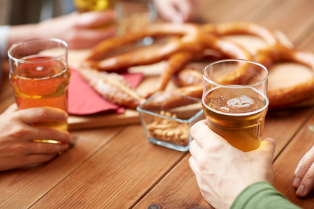 people, leisure and drinks concept - close up of male hands with beer glasses, pretzels and peanuts at bar or pub Stock Photo