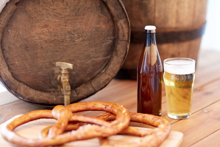 brewery: brewery, drinks and alcohol concept - close up of old beer barrel, glass, bottle and pretzel on wooden table