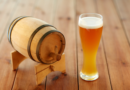 alehouse: brewery, drinks and alcohol concept - close up of draft lager beer in glass and wooden barrel on table
