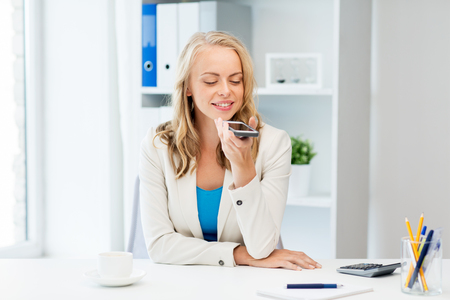 using voice: business, tecnology, communication and people concept - happy businesswoman drinking coffee and using voice command or recorder on smartphone at office