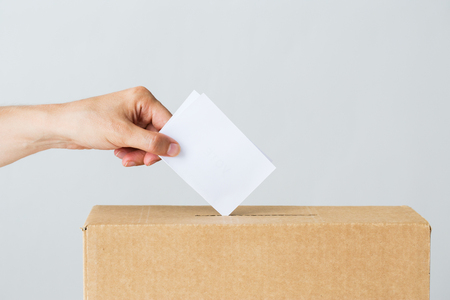voting, civil rights and people concept - male hand putting his vote into ballot box on election Stock Photo