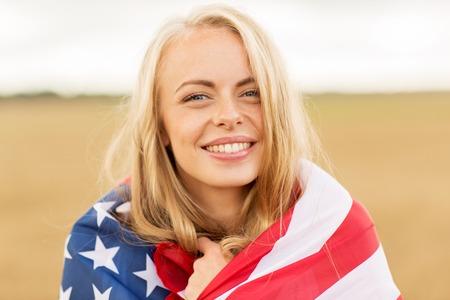 国、愛国心、独立記念日、人々 のコンセプト - 穀物のフィールド上のアメリカ国旗に包まれた若い女性の笑顔は幸せ