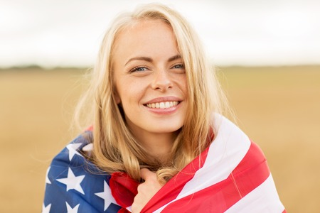 country, patriotism, independence day and people concept - happy smiling young woman wrapped into national american flag on cereal field Archivio Fotografico